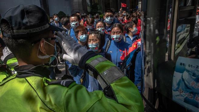 Un policía despide al personal sanitario de la provincia de Shandong en la estación de Wuhan (China), la ciudad epicentro del coronavirus COVID-19, que se prepara para levantar las restricciones impuestas durante dos meses por la pandemia.
