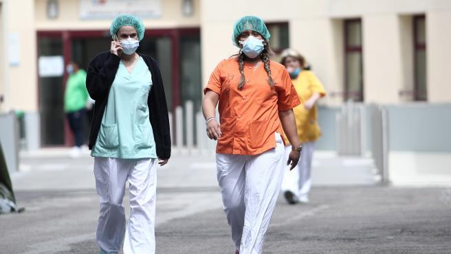 Dos sanitarias protegidas con mascarilla y gorro caminan cerca del Hospital de campaña en las inmediaciones de las Urgencias del Gregorio Marañón para la lucha contra el coronavirus, en Madrid (España) a 6 de abril de 2020.