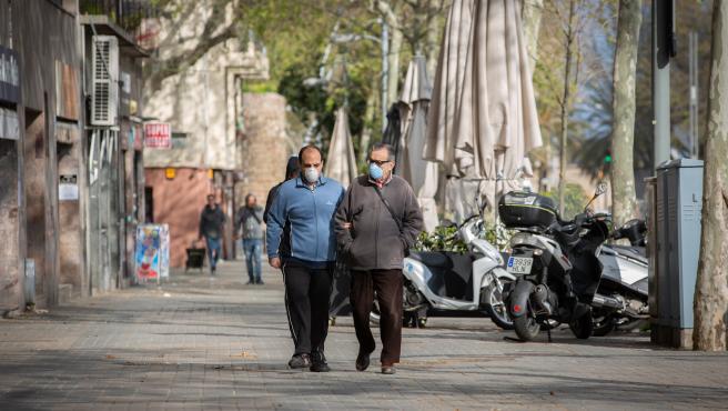 Dos hombres protegidos con mascarillas caminan por una calle durante el noveno día laborable desde que se decretó el estado de alarma en el país a consecuencia del coronavirus, en Barcelona/Catalunya (España) a 26 de marzo de 2020.