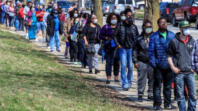 Electores protegidos con mascarillas por la pandemia de coronavirus hacen cola para votar en las elecciones primarias en Milwaukee, Wisconsin (EE UU).