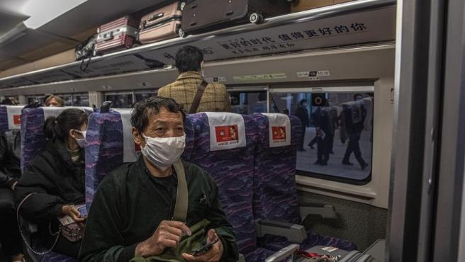 Pasajeros con mascarillas, en el primer tren que salió de la ciudad china de Wuhan tras el levantamiento de la cuarentena impuesta por la pandemia del coronavirus.