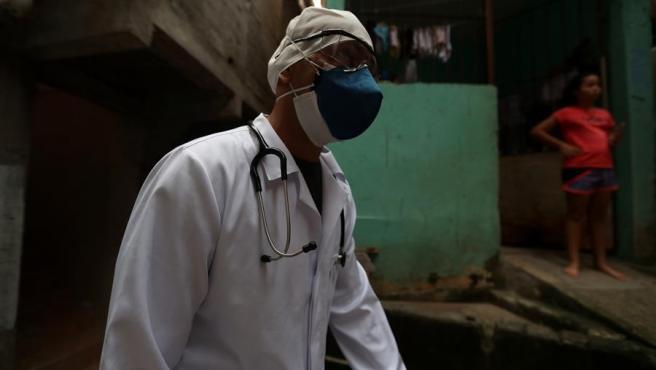 Un médico se dirige a atender a personas con síntomas de COVID-19 en una zona de favelas de Sao Paulo (Brasil).