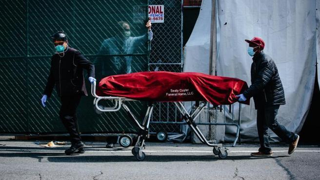 Empleados de un hospital trasladan a un fallecido por COVID-19 desde una morgue temporal a un vehículo funerario en Brooklyn, Nueva York.
