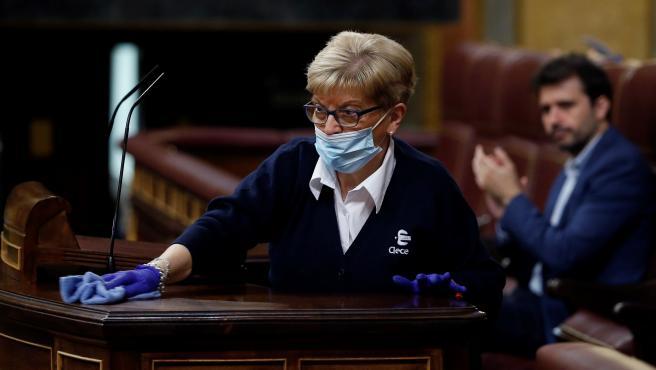 Conchi García, trabajadora del servicio de limpieza del Congreso, desinfecta la tribuna de oradores del hemiciclo tras cada intervención durante el pleno.