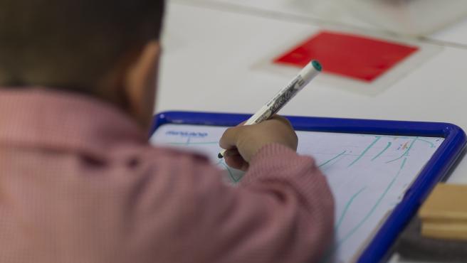 Un niño dibujando en una clase.