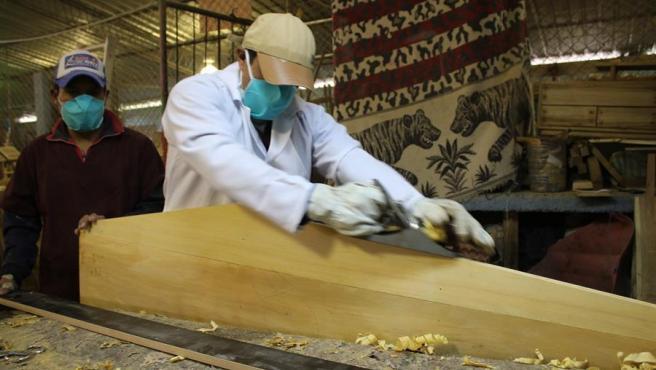 Presos de la cárcel de Ambato (Ecuador) fabrican ataúdes para fallecidos por COVID-19.