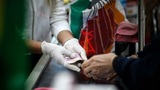 Cajera de un supermercado recibiendo el dinero usando guantes.