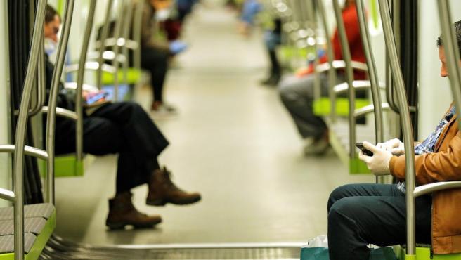 Varias personas miran su móvil en el Metro de Valencia.
