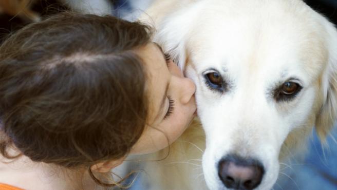 Imagen de una niña besando a su perro.