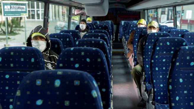 Varios pasajeros guardan la distancia de seguridad sentados en un autobús en Lorca, Murcia.