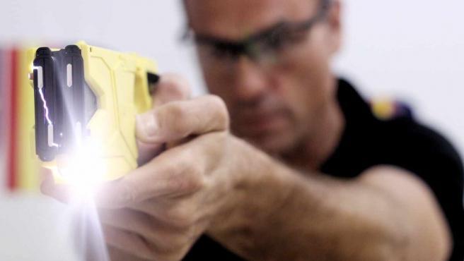 Un policía utilizando una pistola eléctrica.