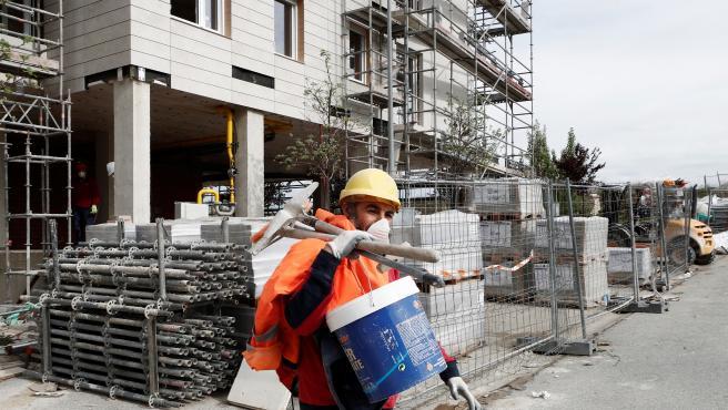 Un trabajador, con la mascarilla puesta, durante su trabajo en edificio de viviendas en construcción, en Pamplona.
