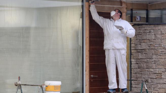 Un operario de la construcción, ataviado con mascarilla, realiza su trabajo en una obra, en una vivienda de Valladolid.