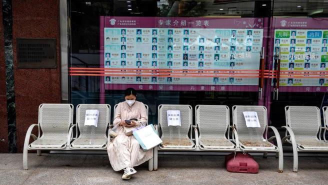 Una mujer espera los resultados de una prueba de COVID-19 en un hospital de Guangzhou, China.
