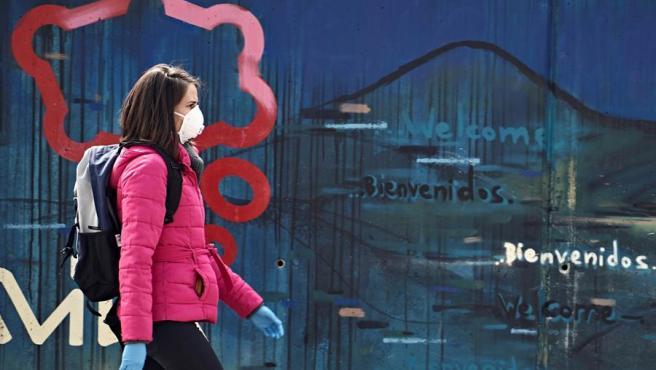 Una mujer con mascarilla y guantes camina por una calle de Ávila este martes durante el vigésimo cuarto día del estado de alarma decretado por el Gobierno por la pandemia del nuevo coronavirus.