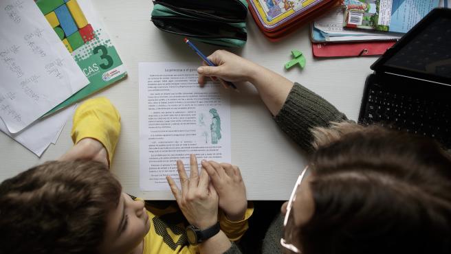 Un niño estudia y hace los deberes en casa con la ayuda de su madre en casa