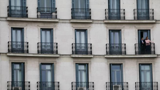 Una pareja conversa en el balcón de su casa en Madrid durante la cuarentena.