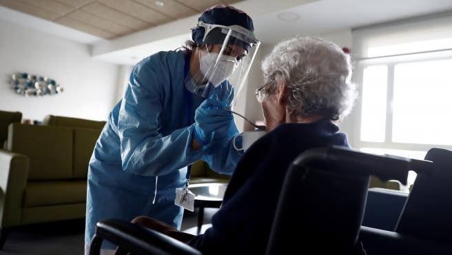 Una cuidadora ayuda a comer a una anciana en una residencia de mayores en Madrid.