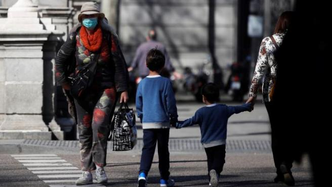 Una mujer con mascarilla junto a dos niños.