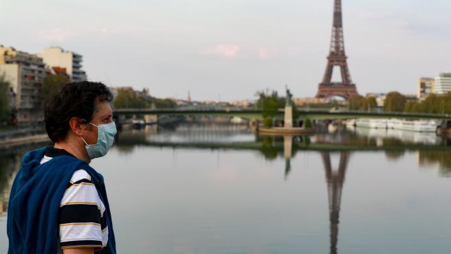 Un hombre con mascarilla frente a la Torre Eiffel en París (Francia).