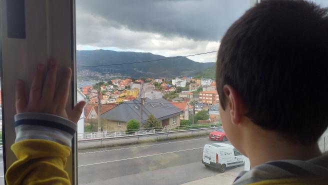 Un niño observa la calle desde el interior de su casa, en pleno confinamiento por el estado de alarma decretado con motivo de la pandemia de coronavirus.