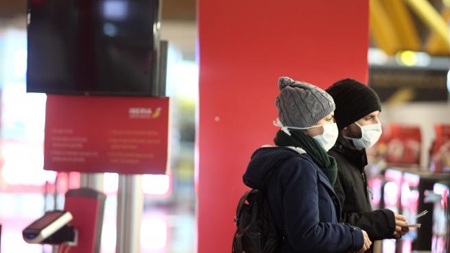 Dos pasajeros protegidos con mascarilla esperan en la Terminal 4 del Aeropuerto Adolfo Suárez Madrid-Barajas
