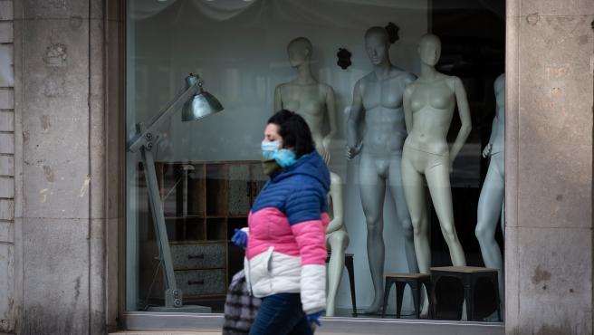 Una mujer protegida con una mascarilla pasa junto a un escaparate de una tienda cerrada en Barcelona durante el estado de alarma por el coronavirus.