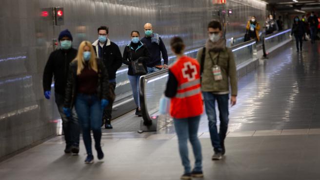Una voluntaria de Cruz Roja entrega mascarillas a los pasajeros en la estación catalana de Diagonal el día en el que se reactiva la actividad laboral no esencial en Cataluña, en Barcelona (Catalunya, España), a 14 de abril de 2020.