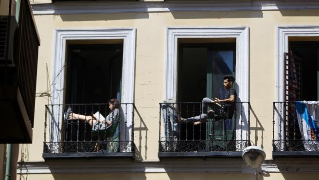 Varias personas sentadas en los balcones de sus casas durante la cuarentena.