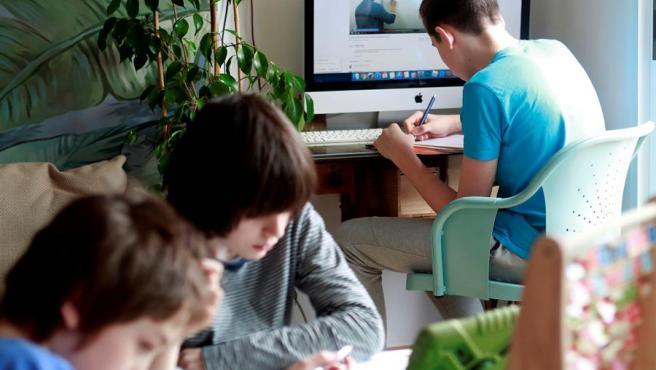 Niños realizan tareas escolares durante el confinamiento por el estado de alarma debido al coronavirus, en Santiago de Compostela.