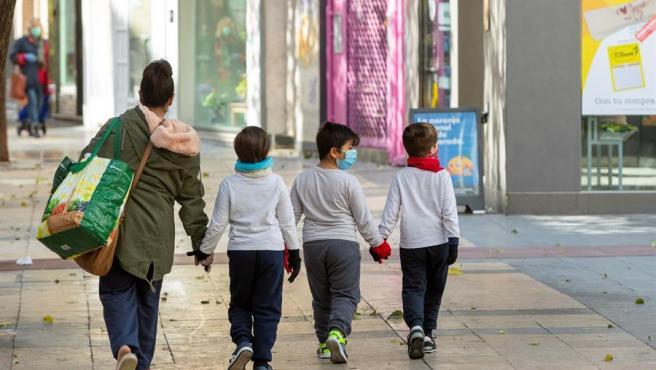 Una madre y sus hijos, con mascarillas, tras hacer la compra en Zaragoza, en una imagen de archivo.