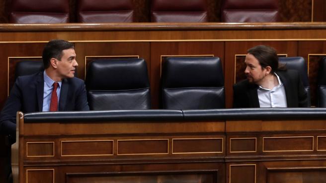 Pedro Sánchez y Pablo Iglesias conversan durante el pleno en el Congreso.