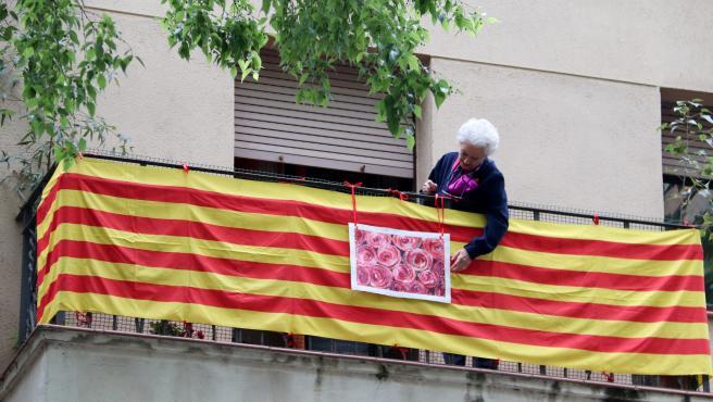 Una dona penja la foto d'unes roses al seu balcó, sobre una senyera, a Barcelona, el 23 d'abril de 2020 (horitzontal).