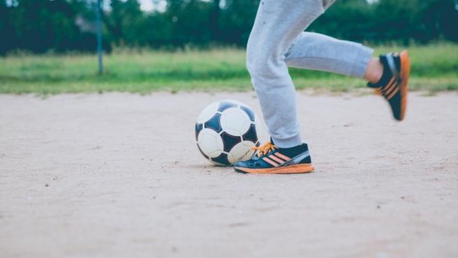 Un niño juega al fútbol