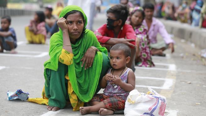 Personas sin hogar de Bangladesh esperan en fila para recibir ayuda durante el cierre nacional impuesto como medida para prevenir la propagación del coronavirus.
