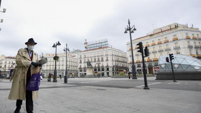 Un hombre camina protegido con mascarilla por la Puerta del Sol de la capital