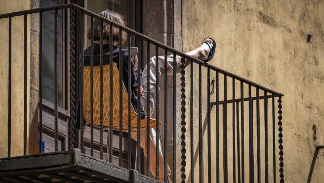 Una joven con el móvil en el balcón de su casa en Barcelona.