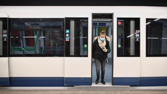 Una mujer protegida con mascarilla se baja de uno de los trenes de Metro de Madrid.