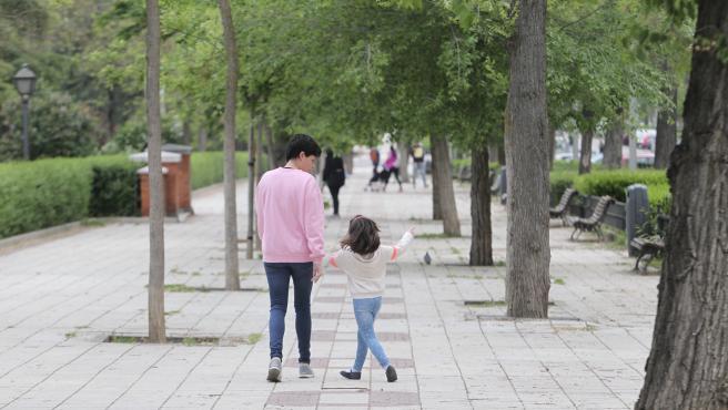 Una madre pasea con su hija en el primer día en que se permiten las salidas de los niños a la calle.