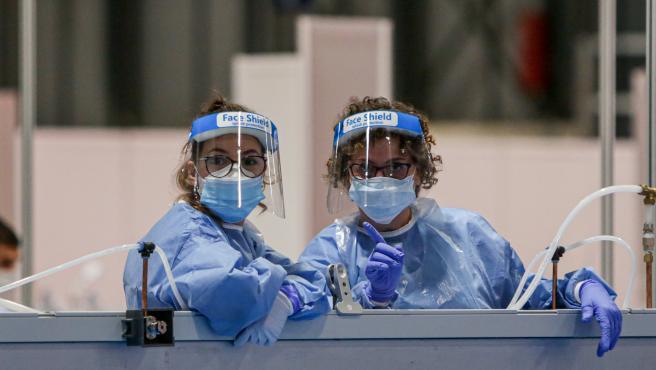 Dos sanitarias protegidas con mascarilla, guantes y pantalla protectora se asoman por encima de una mampara durante la lectura de pasajes de 'El Quijote' para los sanitarios y pacientes del Hospital temporal de IFEMA para enfermos con Covid-1.