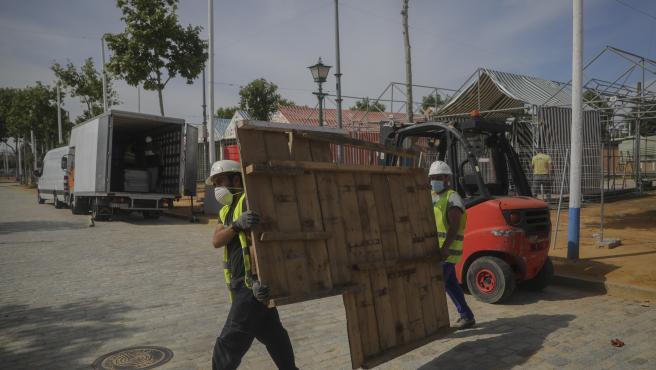 Operarios trabajan en el desmontaje de las instalaciones de la Feria de Abril, suspendida por la pandemia