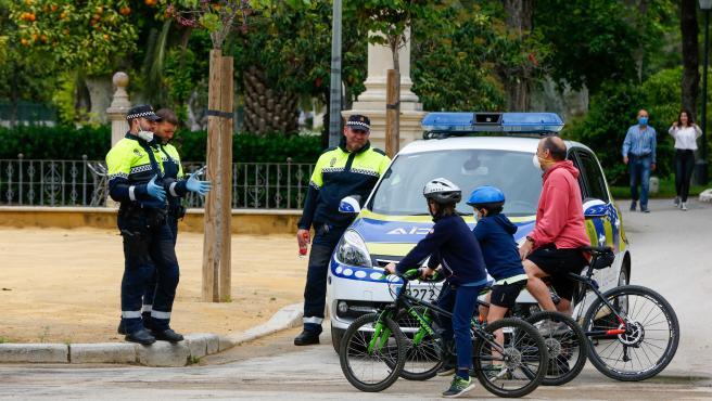 Policías municipales de la capital le explican a un padre las normas de seguridad que hay que respetar debido al estado de alerta por coronavirus en Sevilla.