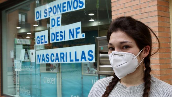 Una mujer con mascarilla ante una farmacia.