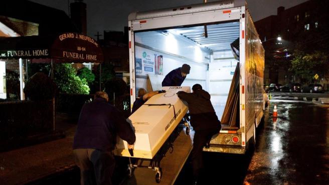 Los directores de funerarias cargan el cuerpo de una víctima de coronavirus, que va a ser cremada en Buffalo, en un camión en las afueras de la funeraria Gerald J. Neufeld en Elmhurst, Nueva York, EE.UU.