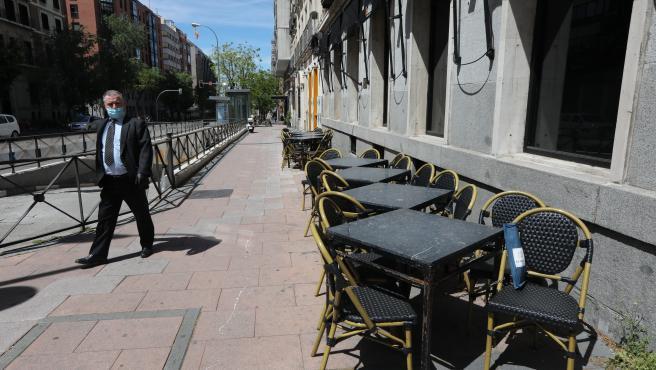 Un hombre con mascarilla pasa junto a una terraza cerrada de un bar.
