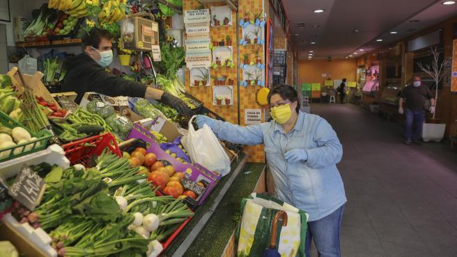 Una mujer protegida con mascarilla compra en una frutería de un mercado