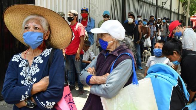Personas sin techo o en condiciones económicas críticas, agravadas por la pandemia del coronavirus, reciben alimentos en una iglesia de Ciudad de México.