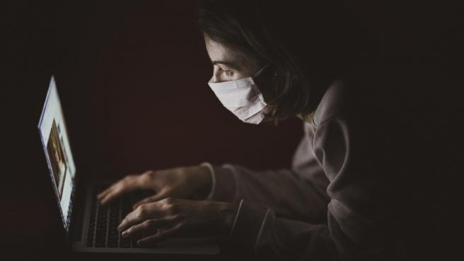 Una mujer con m,ascarilla frente a un ordenador.