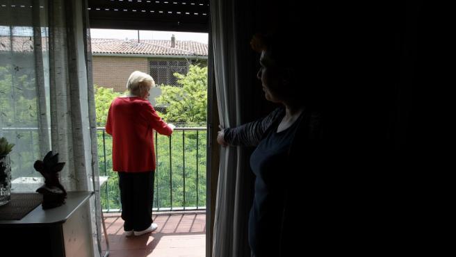 Juana se asoma al balcón de su casa mientras su hija le observa.