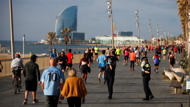 Policías municipales observan a decenas de ciudadanos que dan un paseo o hacen ejercicio por el Paseo Marítimo de Barcelona.